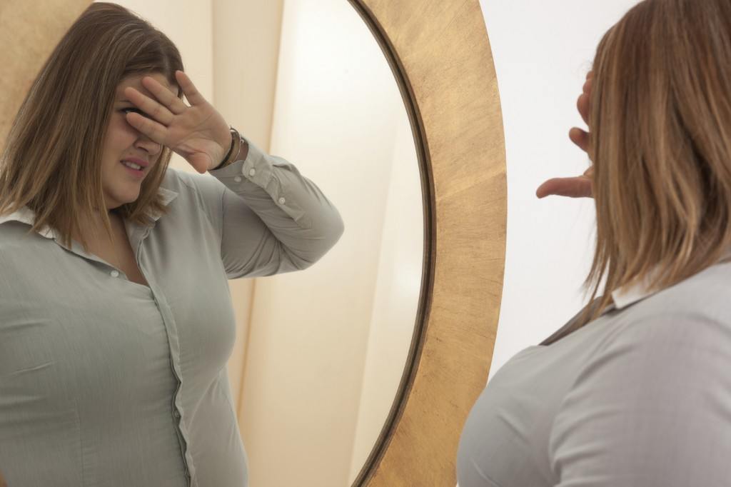 woman rejecting her self-image in the mirror.